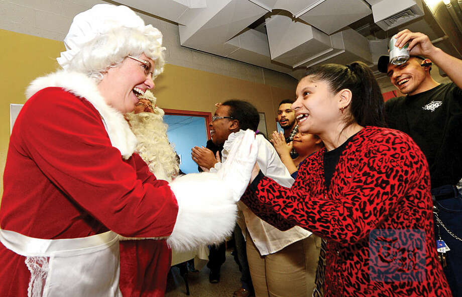 Mrs. Claus, aka Officer Heather Franc, greets Always Reaching for Independence (ARI) clients including Jessie E. as The Stamford Police Association co-hosts the 60th annual holiday party for developmentally disabled teens and adults at ARI of Connecticut, Inc.