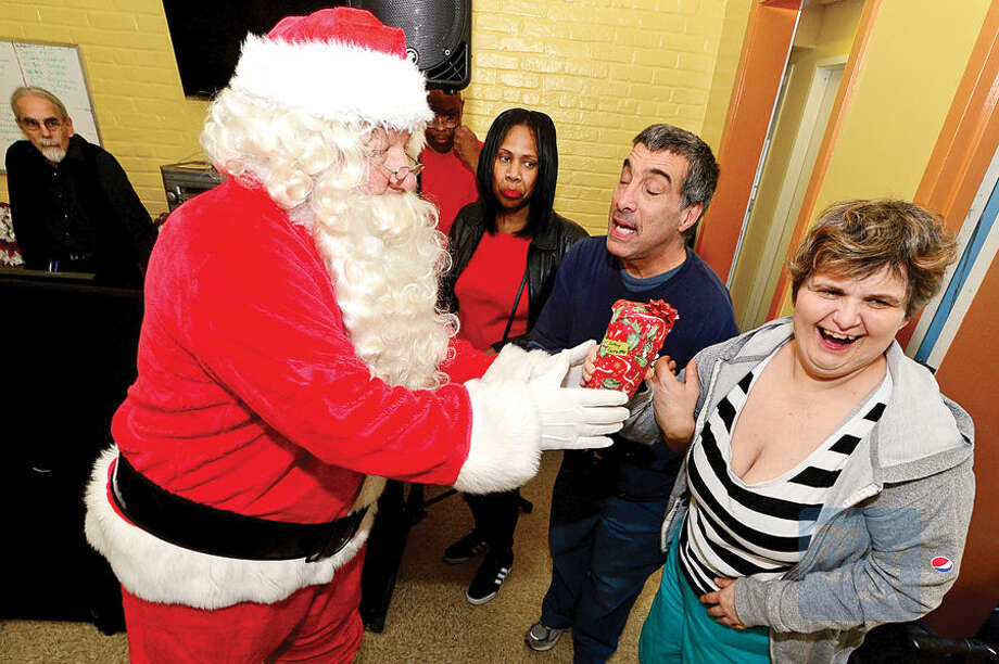 Santa Claus, aka retired police Officer David DeLeo, hands out presents to Always Reaching for Independence (ARI) clients including Cathy C. as the Stamford Police Association co-hosts the 60th annual holiday party for developmentally disabled teens and adults at ARI of Connecticut, Inc.