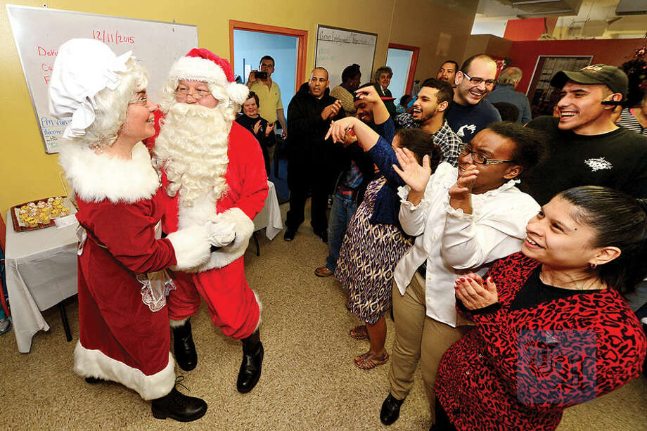 Mrs. Claus, aka police Officer Heather Franc, and Santa Claus, aka retired police Officer David DeLeo, dance for the Always Reaching for Independence (ARI) clients as the Stamford Police Association co-hosts the 60th annual holiday party for developmentally disabled teens and adults at ARI of Connecticut, Inc.