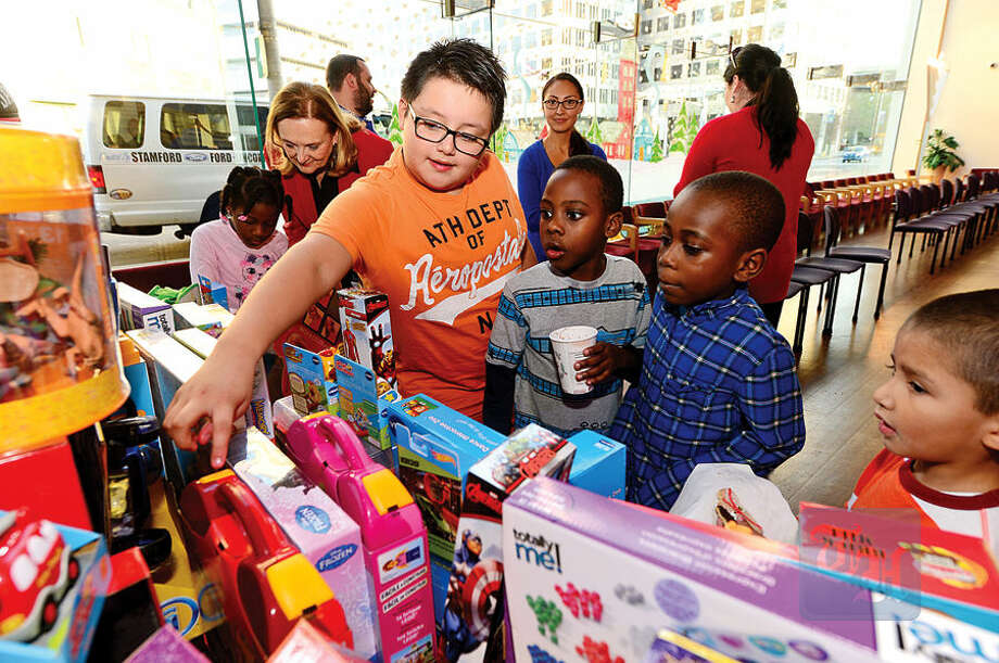 Hour photo / Erik Trautmann NBC staff donate toys to the children from the Stamford Boys and Girls Club including Luis Orellana, 9, Christian Lee Augustine, 8, and Irvin Pierre, 7, at NBC's Stamford Media Center Thursday afternoon.