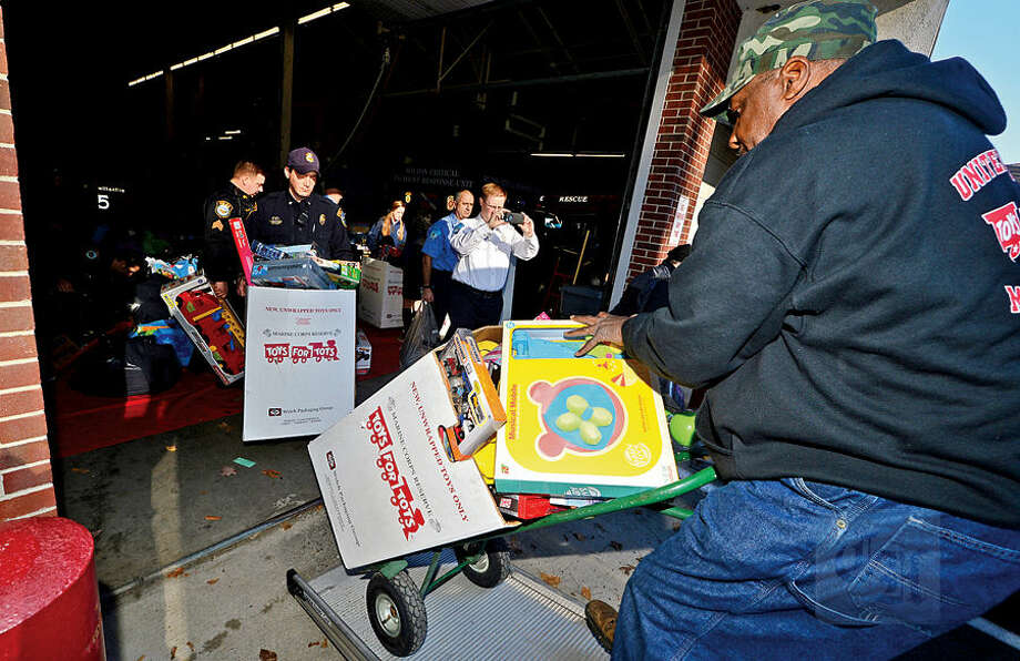 Wilton firefighters, police officers and students from Lady of Fatima School help Toys for Tots volunteers including Ernie Dumas, right, load toys from the donation drop boxes located throughout Wilton at Fire Headquarters Wednesday morning.