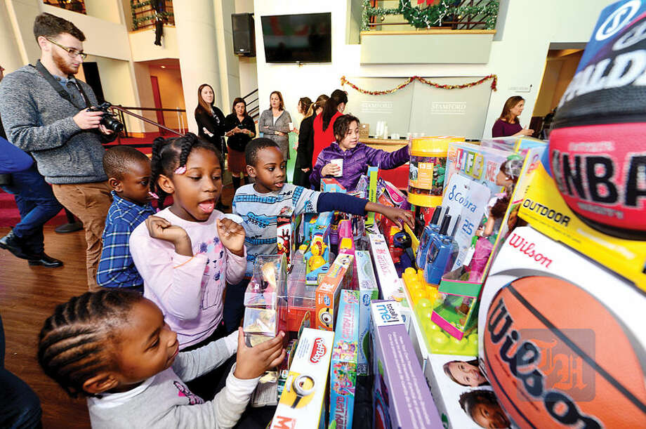 Hour photo / Erik Trautmann NBC staff donate toys to the children from the Stamford Boys and Girls Club at NBC's Stamford Media Center Thursday afternoon.