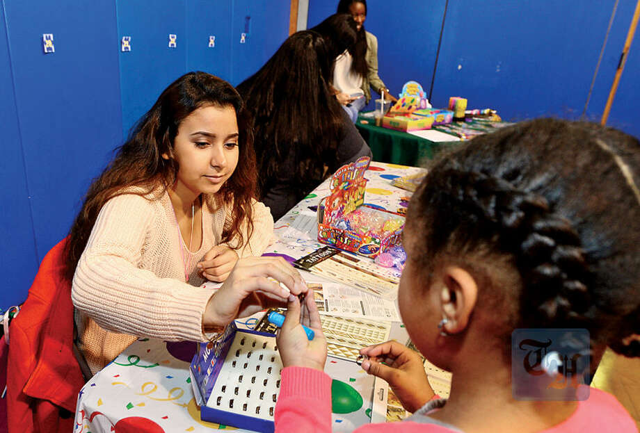 Hour photo / Erik Trautmann Students in the entrepreneurship program at Norwalk High School including Magaly Anguiano sell items to Naramake Elementary School students like kindergartner Biana Ruffin.