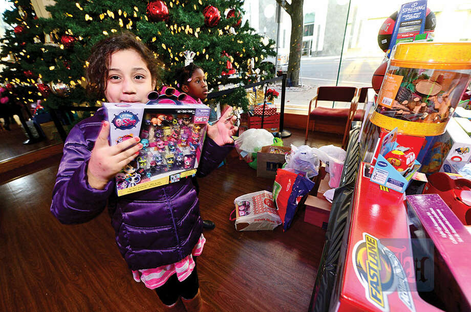Hour photo / Erik Trautmann NBC staff donate toys to the children from the Stamford Boys and Girls Club including Catherine Garcia, 8, at NBC's Stamford Media Center Thursday afternoon.