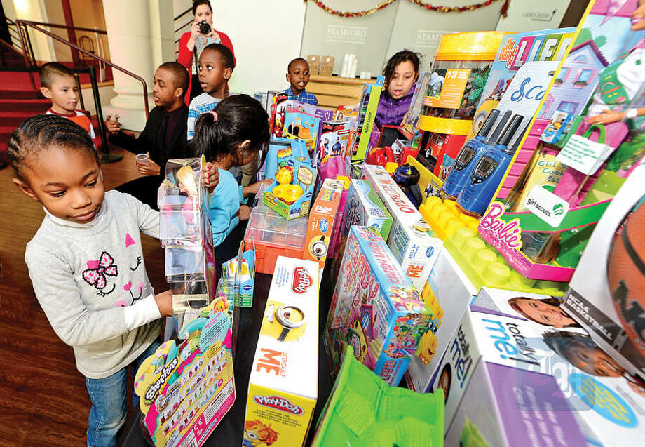 NBC staff donate toys to the children from the Stamford Boys and Girls Club including Myla Rose Rivers, 5, at left, at NBC's Stamford Media Center Thursday afternoon.