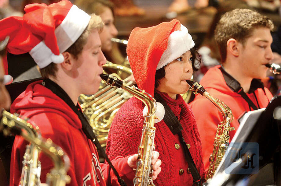 Hour photo / Erik Trautmann Brien McMahon High School saxophone player Margarette Cabangbang, center, practices with the orchestra for their annual Poinsettia winter concert on Tuesday, Dec. 15 at 7 p.m.