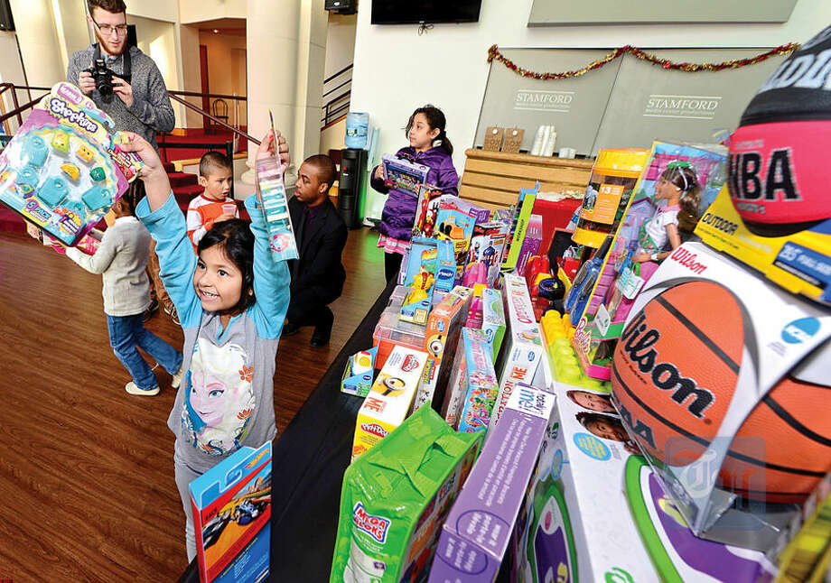 Hour photo / Erik Trautmann NBC staff donate toys to the children from the Stamford Boys and Girls Club including Kimberly Torres, 5, at NBC's Stamford Media Center Thursday afternoon.