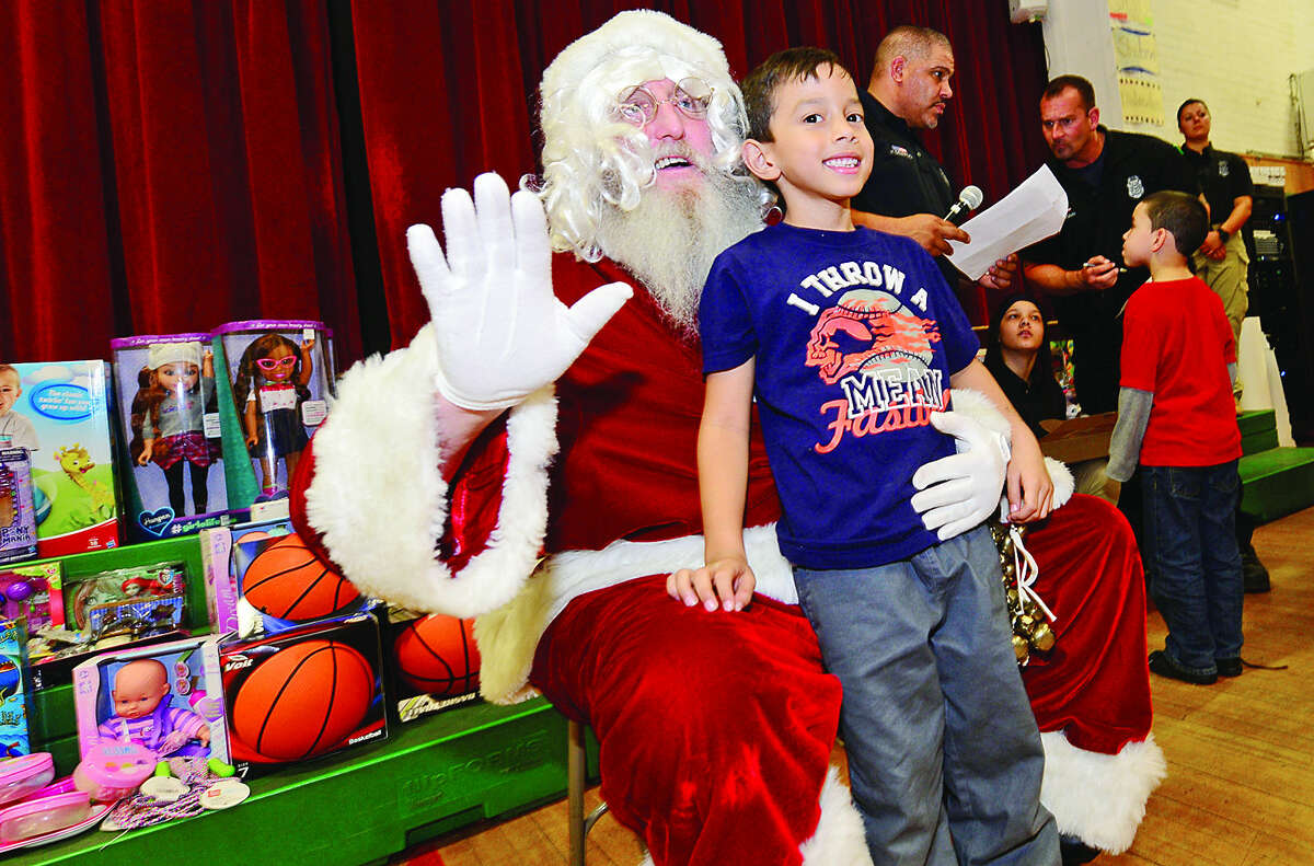 Hour photo / Erik Trautmann Santa Claus, aka retired police officer Joe Kubik, poses for a picture with 6 year old Rubin Oliva during The Norwalk Community Policing Division Children's Christmas Party Saturday at Columbus Magnet School.