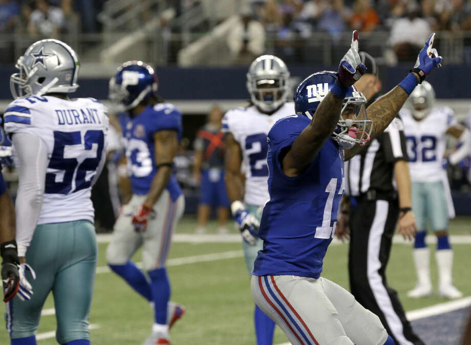 New York Giants' Odell Beckham (13) celebrates after grabbing a touchdown pass as Dallas Cowboys' Justin Durant (52) walks away during the second half of an NFL football game, Sunday, Oct. 19, 2014, in Arlington, Texas. (AP Photo/LM Otero)