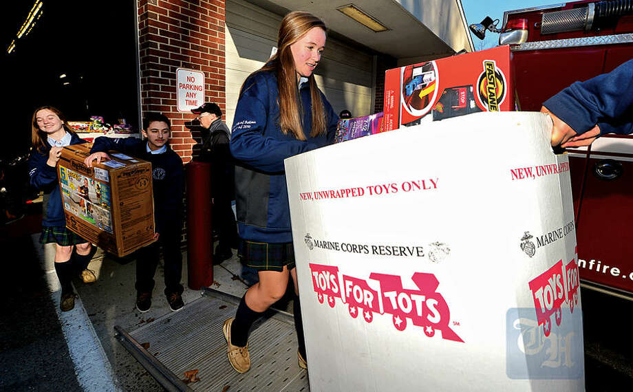 Wilton firefighters, police officers and students from Lady of Fatima School including 8th-grader Nancy Lynch help Toys for Tots volunteers load toys from the donation drop boxes located throughout Wilton at Fire Headquarters Wednesday morning.