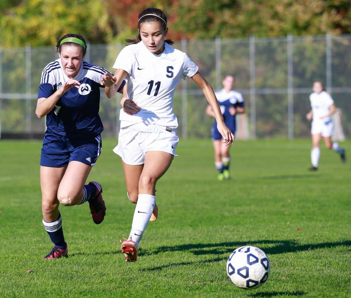 Hour photo/Chris Palermo Wilton's Hayley English and Staples' Tia Zajec race for the ball during the Wrecker's win over Wilton Saturday afternoon.