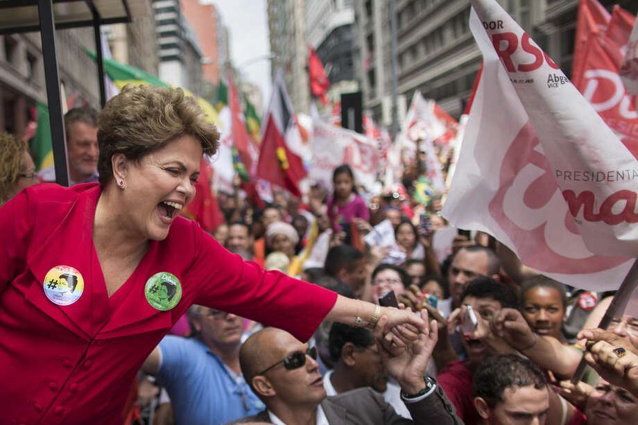 Brazil's President and Workers Party candidate Dilma Rousseff greets supporters during a rally for her re-election campaign in Porto Alegre, Brazil, Saturday, Oct. 25, 2014. Rousseff and Neves are in a tight election contest, that culminates Sunday when millions of Brazilians are expected to go to the polls and decide who'll be the next leader of Latin America's biggest economy. (AP Photo/Felipe Dana)