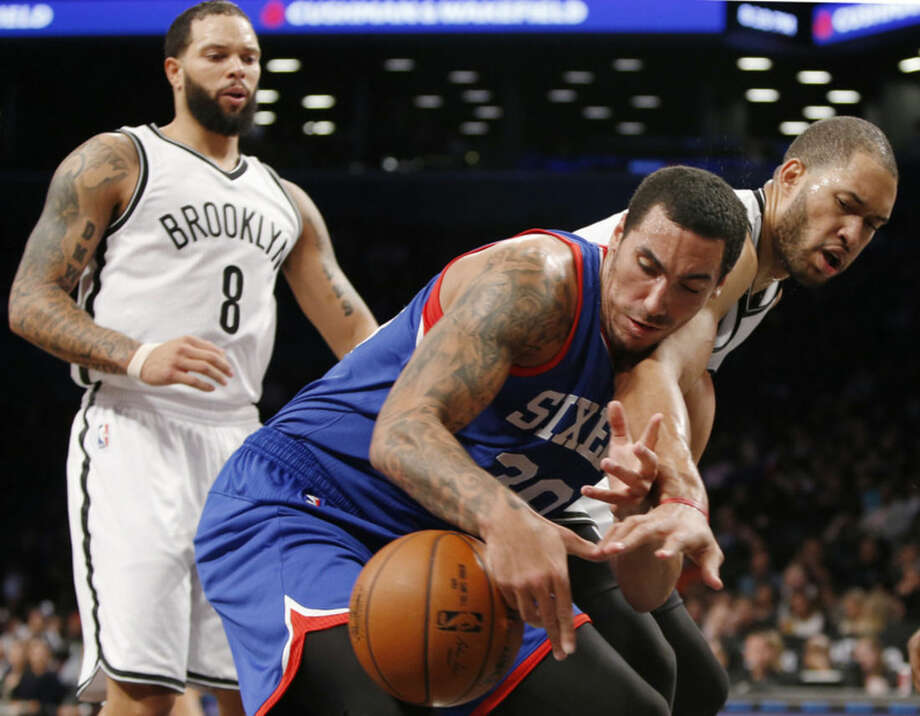 Brooklyn Nets guard Deron Williams (8), left, watches as Nets center Jerome Jordan, right, strips the ball from Philadelphia 76ers forward Drew Gordon (30) in the first half of an NBA basketball game at the Barclays Center, Monday, Oct. 20, 2014, in New York. (AP Photo/Kathy Willens)