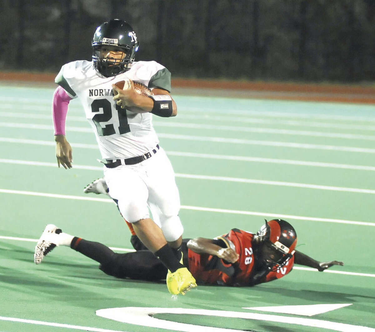 Hour photo/John Nash Norwalk running back Eric Cohens (21) scampers for a big gain during Friday's FCIAC football game at Bridgeport Central. Cohens had 243 all-purpose yards, helping Norwalk post a 36-20 win.