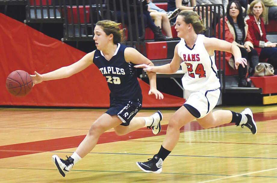 Hour photo/John Nash - Staples' Christine Taylor, left, picks up a loose ball on the run as New Canaan defender Kylie Murphy tracks her down during Thursday's girls basketball game in New Canaan.