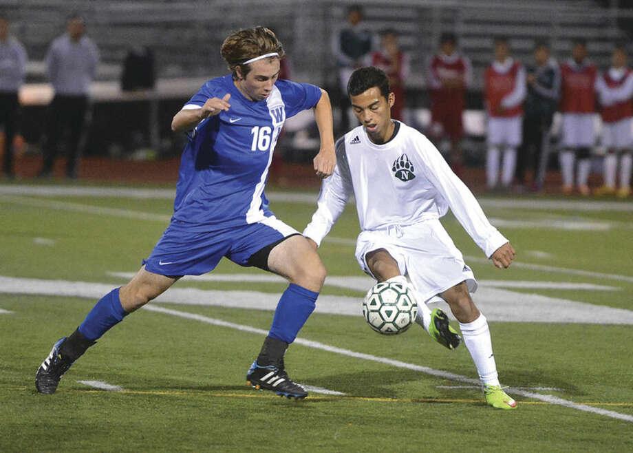 Hour photo/Alex von KleydorffNorwalk's Anthony Hernandez kicks the ball past Darien's Jack Kniffen during Friday night's game.