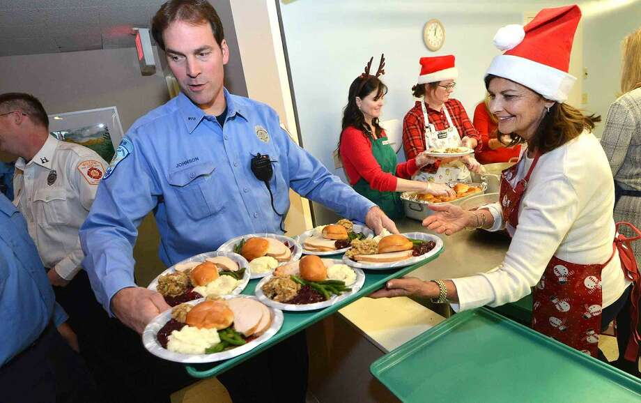 Wilton Firefighter Glenn Johnson grabs a tray filled with turkey dinners prepared by The Wilton Womens Club for residents and guests at the Ogden House Holiday Luncheon.