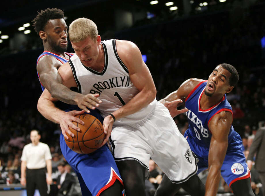 Philadelphia 76ers guard Tony Wroten, left, gets tangled up with Brooklyn Nets forward Mason Plumlee (1) as Philadelphia 76ers forward Brandon Davies (0) defends in the second half of an preseason NBA basketball game at the Barclays Center, Monday, Oct. 20, 2014, in New York. The Nets defeated the Sixers 99-88. (AP Photo/Kathy Willens)