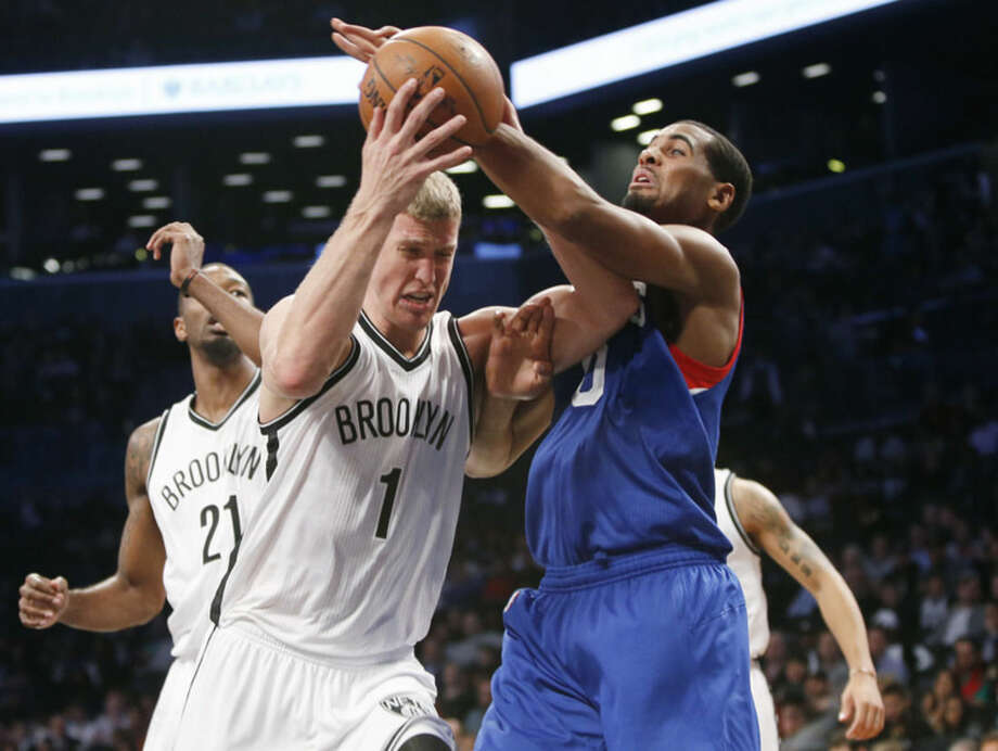 Brooklyn Nets forward Mason Plumlee (1) struggles to hold onto the ball after pulling a rebound as Philadelphia 76ers forward Brandon Davies (0) tries to strip the ball from him in the first half of an NBA basketball game at the Barclays Center, Monday, Oct. 20, 2014, in New York. (AP Photo/Kathy Willens)