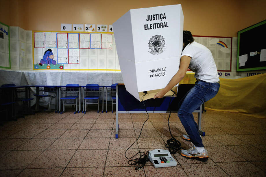 An electoral worker assembles a voting station at a school in Brasilia, Brazil, Saturday, Oct. 25, 2014. Brazilians will go to the polls on Sunday to decide who'll be the next leader of Latin America's biggest economy. (AP Photo/Eraldo Peres)