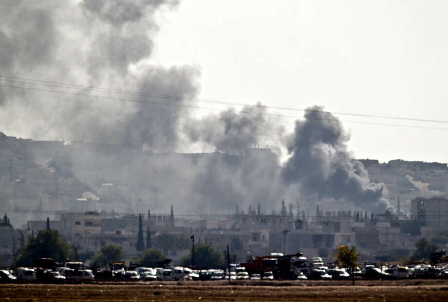 Smoke rises during fighting in Kobani, seen from the outskirts of Suruc, near the Turkey-Syria border, Saturday, Oct. 25, 2014. Kobani, also known as Ayn Arab, and its surrounding areas, has been under assault by extremists of the Islamic State group since mid-September and is being defended by Kurdish fighters. (AP Photo/Vadim Ghirda)