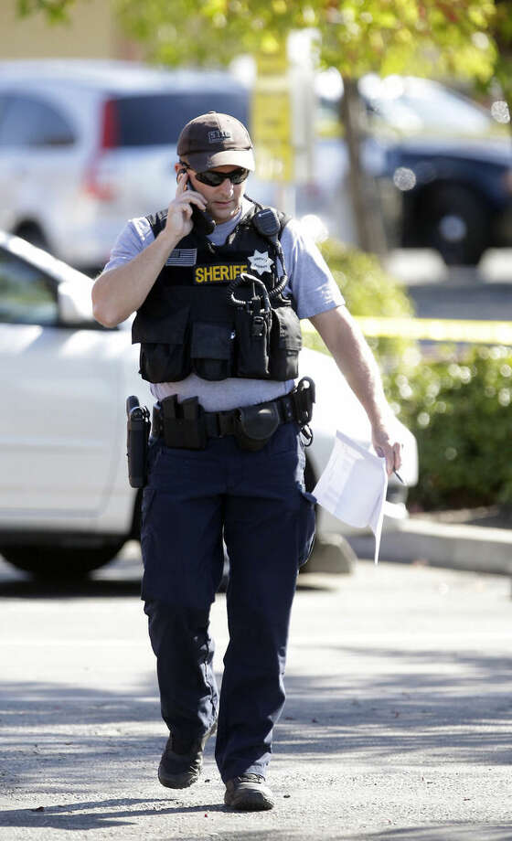 A Sacramento County Deputy Sheriff talks on a mobile phone at the site where a deputy was shot by an assailant who then carjacked two vehicles prompting a manhunt in Sacramento, Calif., Friday, Oct. 24, 2014. The deputy was taken to a hospital but his condition is not immediately known.(AP Photo/Rich Pedroncelli)