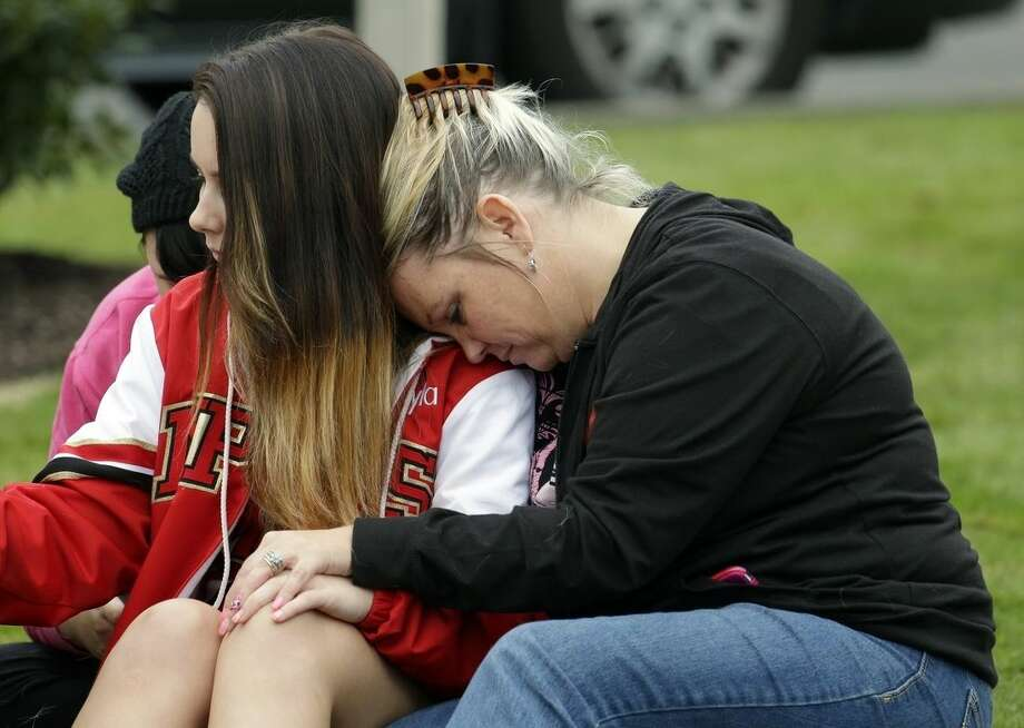 Peggy Ray, right, hugs her daughter, Shayla Kline, 15, Friday, Oct. 24, 2014, at a church where students were taken following a shooting at Marysville Pilchuck High School in Marysville, Wash. (AP Photo/Ted S. Warren)
