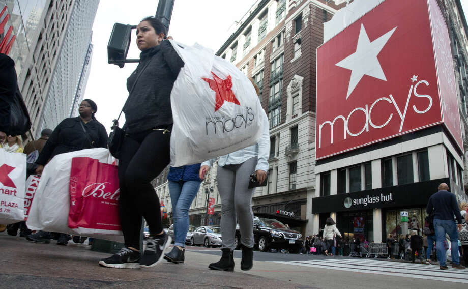 FILE - In this Nov. 27, 2015 file photo, shoppers carry bags as they cross a pedestrian walkway near Macy's in Herald Square in New York. The unseasonably warm weather has left some people feeling cold about holiday shopping. Sales of cold-weather items have been particularly icy. Sales of women's boots in New York, are down 24 percent for the first half of December, according to Planalytics, a weather forecasting firm for retailers. (AP Photo/Bebeto Matthews)