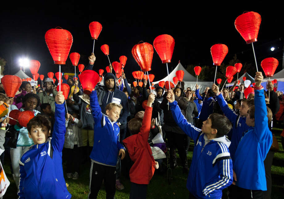 Hour photo/Chris PalermoSupporters hold up their red lanterns, which symbolize their support for those with blood cancer at the Light the Night Friday at Calf Pasture Beach.