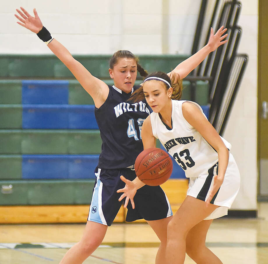Hour photo/John Nash - Wilton's Hana Previte, left, guards New Milford's Isabel Feliz during the first half of Friday's game in New Milford.