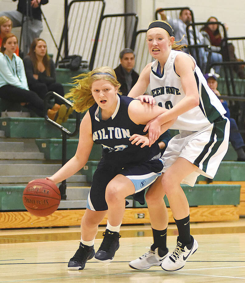 Hour photo/John Nash - Wilton's Claire Gulbin, left, drives past New Milford's Abbi Debes during the first half of Friday's season-opening game in New Milford.
