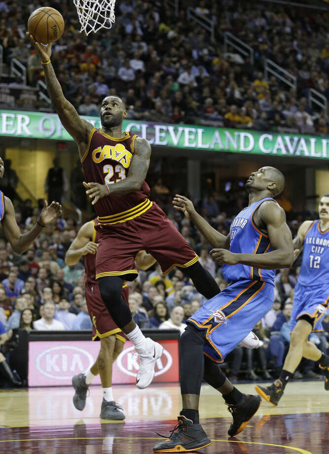 Cleveland Cavaliers' LeBron James, left, drive to the basket as Oklahoma City Thunder's Serge Ibaka, right, from the Republic of Congo, watches in the second half of an NBA basketball game ,Thursday, Dec. 17, 2015, in Cleveland. The Cavaliers won 104-100. (AP Photo/Tony Dejak)