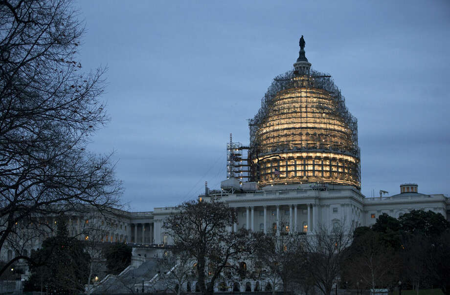 The Capitol Dome is illuminated amid scaffolding for repairs in Washington, Friday morning, Dec. 18, 2015. The House and Senate race to wrap up votes on a massive spending and tax package, which President Barack Obama promises to sign. (AP Photo/J. Scott Applewhite)