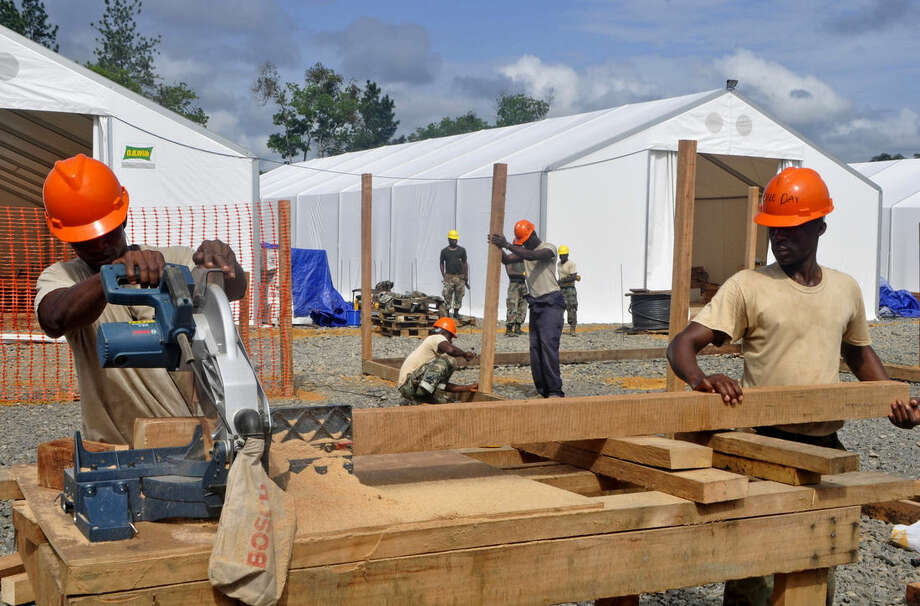 In this photo taken on Friday, Oct. 24, 2014, Liberian troops work to build a new section of an Ebola treatment center in the town of Tubmanburg, situated on the outskirts of the capital Monrovia, Liberia. More than 10,000 people have been infected with Ebola, according to figures released Saturday, Oct. 25, 2014 by the World Health Organization, as the outbreak continues to spread. Of those cases, 4,922 people have died. (AP Photo/Abbas Dulleh)