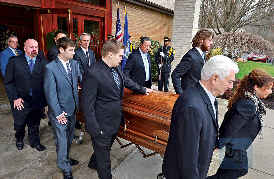 Hour photo / Erik Trautmann Pallbearers escort the casket during the recessional as family, friends and dignitaries mourn the loss of State Representative and Soundkeeper Terry Backer following his memorial service at St. Matthew Church in Norwalk Friday morning.