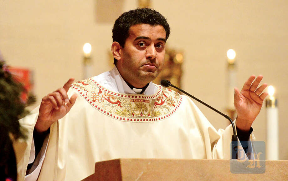 Hour photo / Erik Trautmann Father Sunil Pereira of St. Matthew's Church conducts mass as family, friends and dignitaries mourn the loss of State Representative and Soundkeeper Terry Backer during his memorial service at St. Matthew's in Norwalk Friday morning.