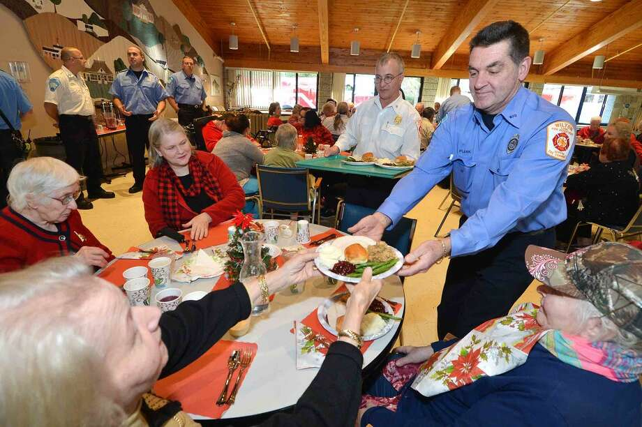 Hour Photo/Alex von Kleydorff Wilton Firefighter Kevin Plank along with Wilton's Career Firefighters serve a Turkey feast to 100 residents and guests during the Ogden House Holiday Luncheon, the 30th year they have done so