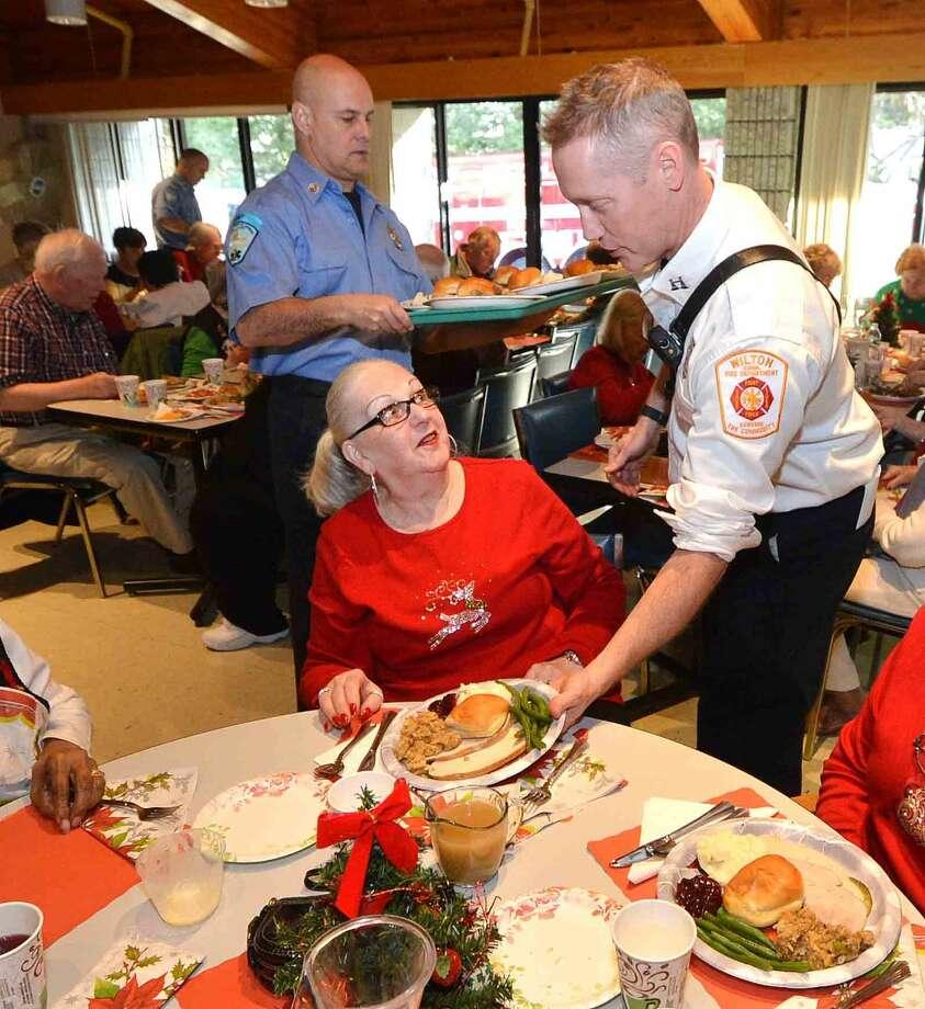 Hour Photo/Alex von Kleydorff Wilton Career Firefighters serve the Holiday Lunch at Ogden House