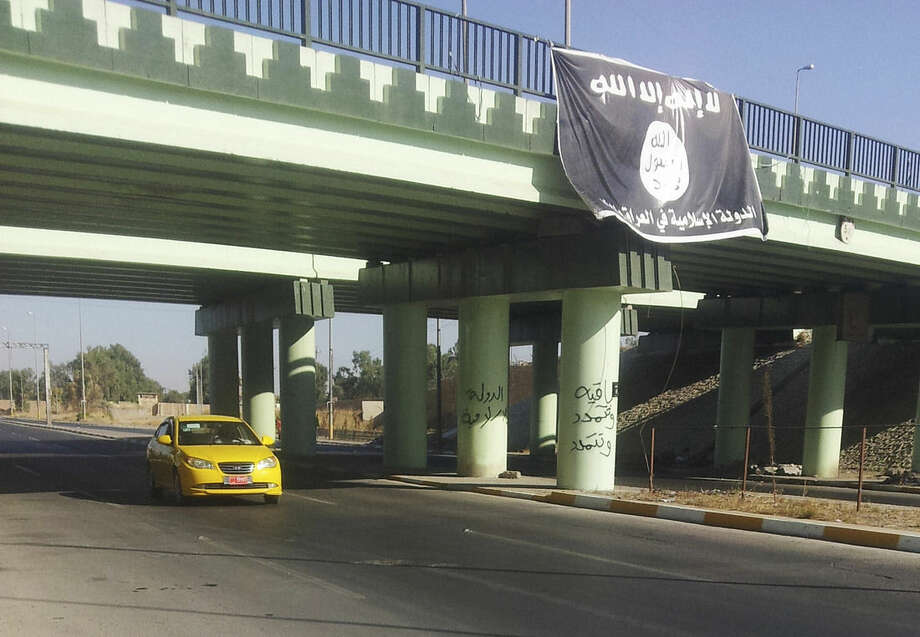 FILE - In this file photo taken Monday, July 28, 2014, a motorist passes by a flag of the Islamic State group at the entrance of the northern Iraqi city of Mosul, Iraq. The Islamic state group has accelerated killings of former policemen and army officers, apparently fearing they might join a potential internal Sunni uprising against its rule. Such killings, including the deadly attack on police Col. Mohammed Hassan and his son in mid October, have accelerated in recent days, as the extremists' opponents - Kurdish fighters and Shiite militias, backed by U.S.-led airstrikes - have made some gains, taking back several towns that the militants had overrun. (AP Photo, File)