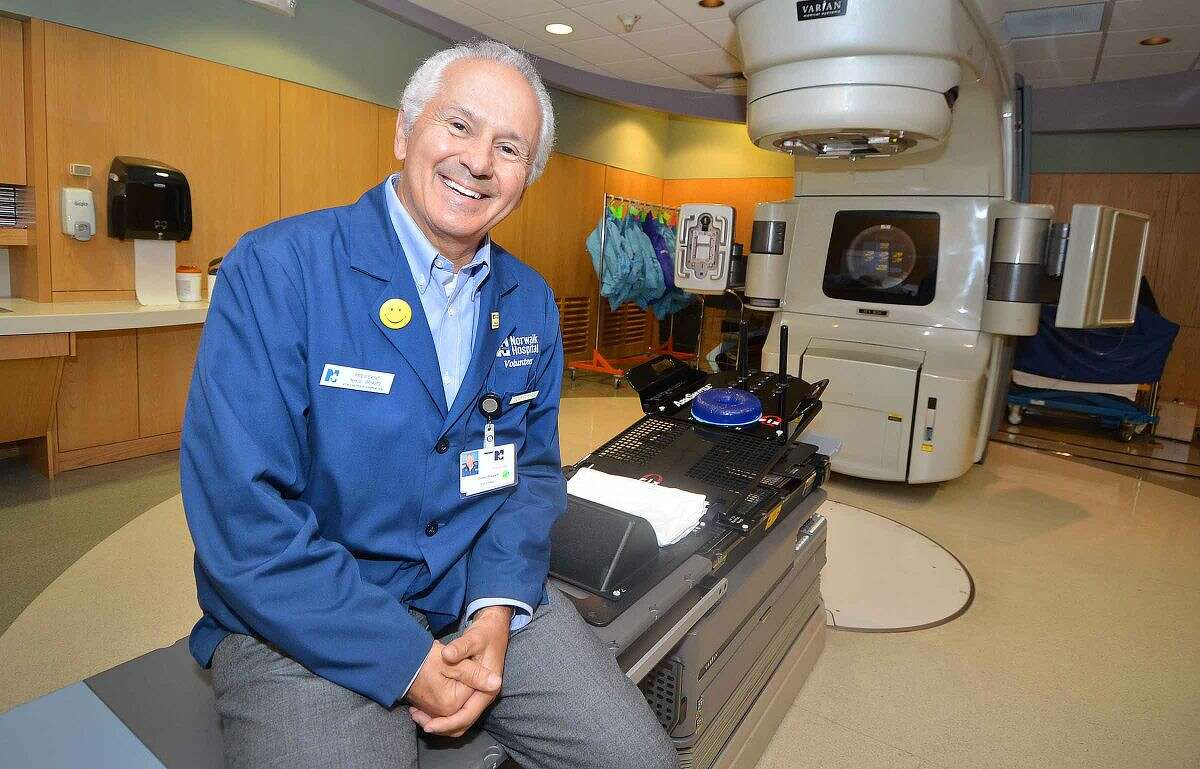 Hour Photo/Alex von Kleydorff Norwalk Hospitals President of the Volunteers and a volunteer himself with some 600 hours Corky Stewart in the Main Radiation Treatment room where he works with patients