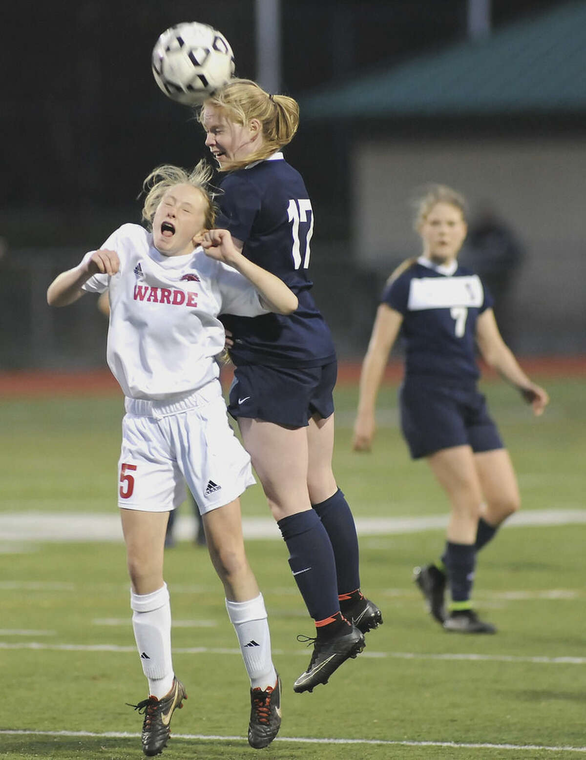 Hour photo/John Nash Wilton's Maggie Walsh (17) gets more air than Fairfield Warde's Lauren Tangney to win an air ball during Wednesday's FCIAC championship game in Norwalk. The two teams were declared co-champs after the game ended in a 1-1 tie.