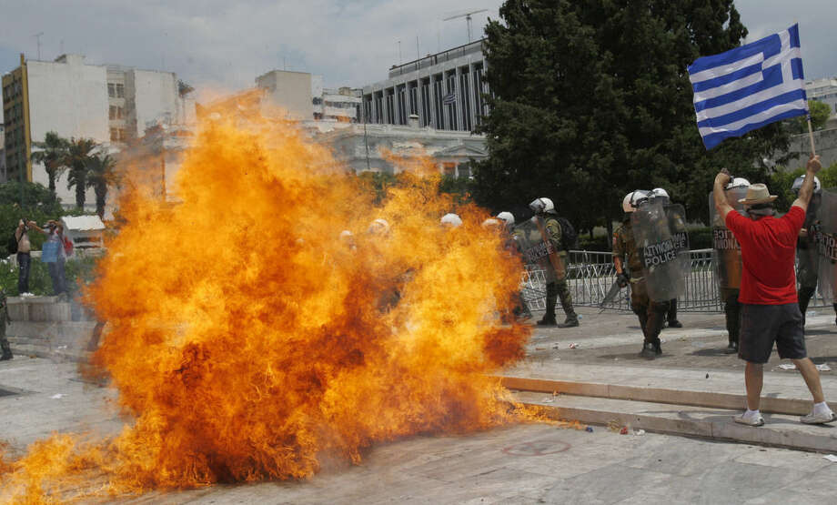 FILE - In this Wednesday, June 29, 2011 file photo, a fire bomb explodes next to riot police at Syntagma Square in front of the Greek Parliament in central Athens, Greece. While many parts of Europe, notably Greece, were struggling under the weight of their debts, the European Central Bank was raising interest rates. Hindsight suggests the increases were mistaken and the bank was back cutting rates by the end of 2011. On Wednesday, Dec. 16, 2015, the US Federal Reserve is expected to raise interest rates for the first time since 2006. (AP Photo/Petros Karadjias, File)