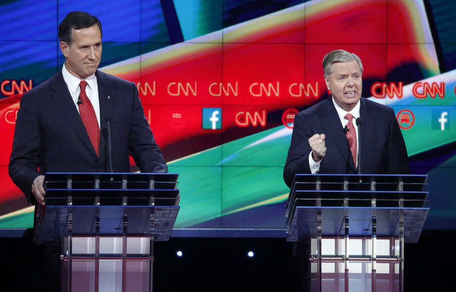Lindsey Graham, right, makes a point as Rick Santorum looks on during the CNN Republican presidential debate at the Venetian Hotel & Casino on Tuesday, Dec. 15, 2015, in Las Vegas. (AP Photo/John Locher)