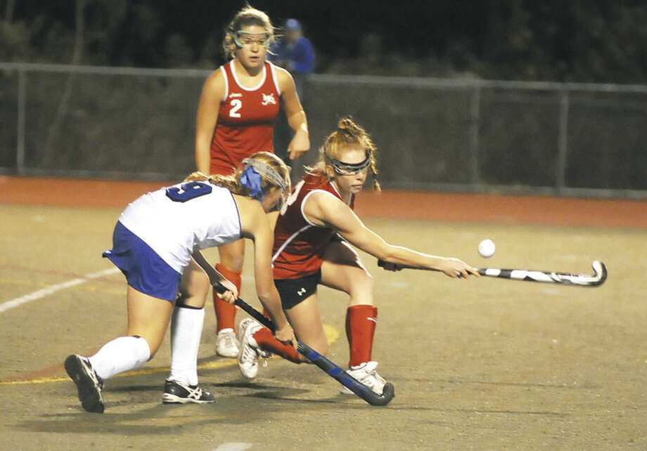 Hour photo/John NashNew Canaan's Elizabeth Miller, right, hits the ball away from Darien's Hannah McLane as Rams' Catherine Granito (2) looks on during Thursday's FCIAC field hockey championship game at Casagrande Field in Norwalk.