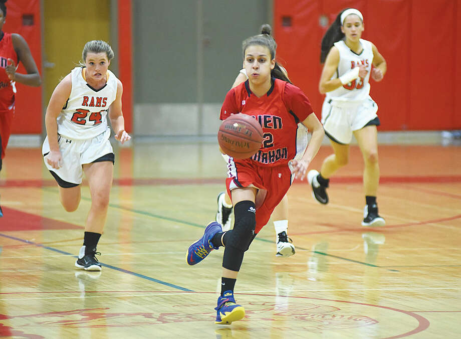 Hour photo/John Nash - Brien McMahon's Michelle Perea, center, pushes the ball up court ahead of New Canaan's Kylie Murphy, left, and Ellie Aliapoulios during Tuesday's season-opening game in New Canaan. McMahon won, 25-23.