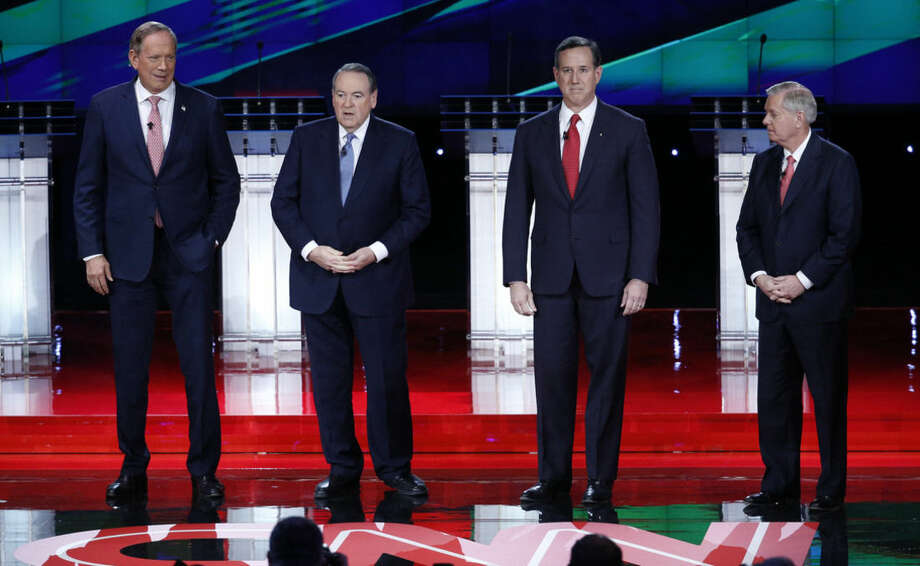 Republican presidential candidates, from left, George Pataki, Mike Huckabee, Rick Santorum, and Lindsey Graham take the stage during the CNN Republican presidential debate at the Venetian Hotel & Casino on Tuesday, Dec. 15, 2015, in Las Vegas. (AP Photo/Mark J. Terrill)