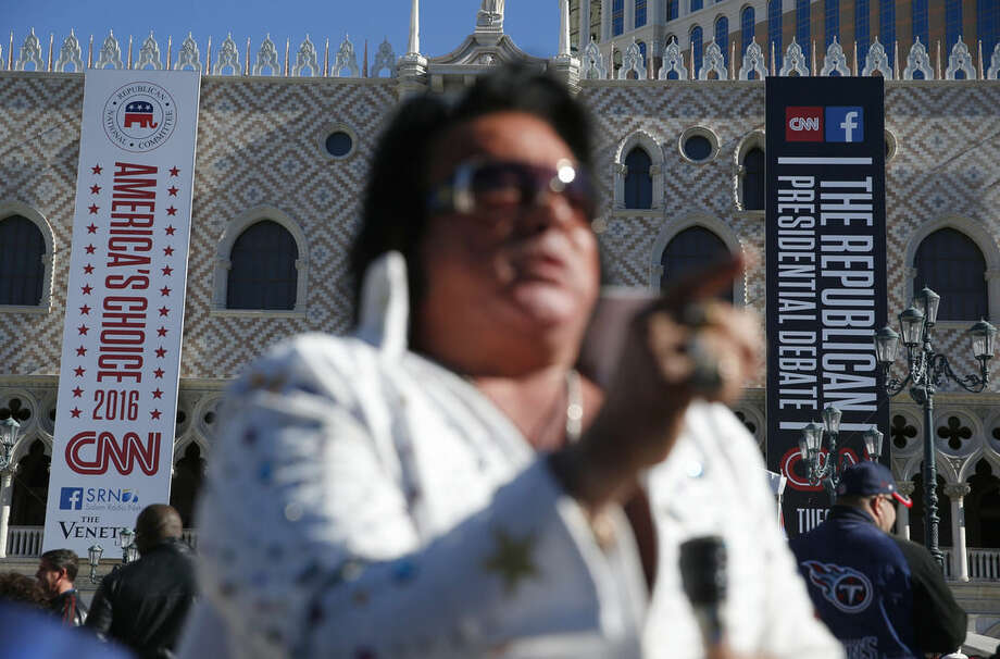 An Elvis impersonator performs outside the Venetian Hotel & Casino before the CNN Republican presidential debate on Tuesday, Dec. 15, 2015, in Las Vegas. (AP Photo/John Locher)