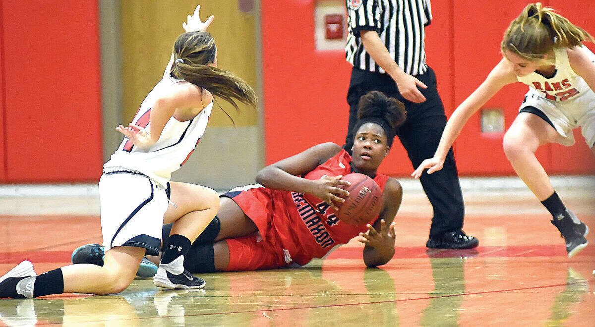 Hour photo/John Nash - McMahon's Ajia Andrews, center, comes up with a loose ball and looks for options before New Canaan's Kylie Muprhy, left, and Leigh Charlton, right, can close in. McMahon won the game 25-23.