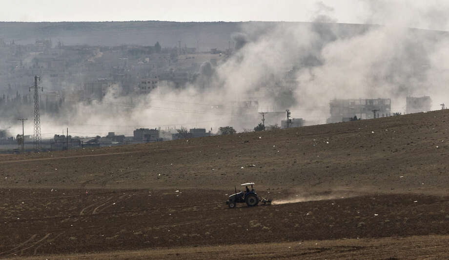 A man ploughs a field as smoke rises from the town of Kobani during airstrikes by the US led coalition, seen from the outskirts of Suruc, near the Turkey-Syria border, Tuesday, Oct. 28, 2014. Kobani, also known as Ayn Arab, and its surrounding areas, has been under assault by extremists of the Islamic State group since mid-September and is being defended by Kurdish fighters. (AP Photo/Vadim Ghirda)