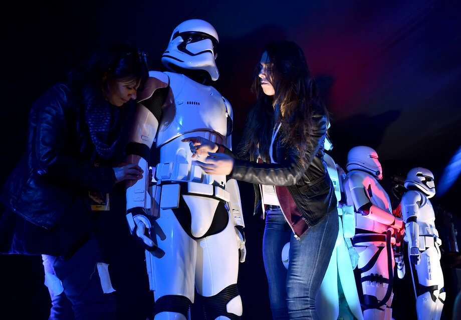 """Staff members prepare Stormtrooper characters on the red carpet at the world premiere of """"Star Wars: The Force Awakens"""" at the TCL Chinese Theatre on Monday, Dec. 14, 2015 in Los Angeles. (Photo by Jordan Strauss/Invision/AP)"""